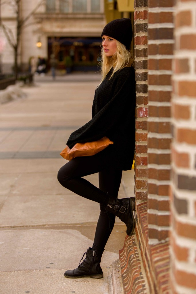 Black sweater, black leggings, brown clutch